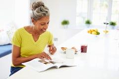 Femme mangeant le petit déjeuner et lisant le magazine photographie stock