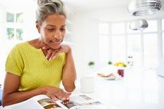 Femme mangeant le petit déjeuner et lisant le magazine photo stock