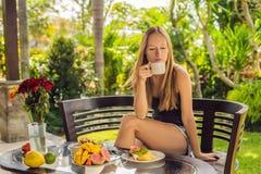 Femme mangeant le petit déjeuner sur la terrasse Cette poussée d'énergie pour la journée entière images libres de droits