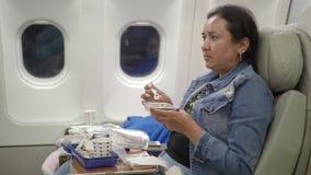 Femme mangeant le repas sur l'avion commercial 4K banque de vidéos