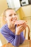 Femme mangeant le sandwich à la maison images libres de droits