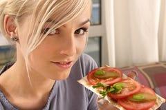 Femme mangeant un sandwich à tomate Photographie stock