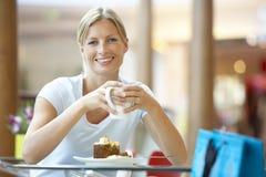 Femme mangeant une partie de gâteau au mail image libre de droits