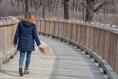 Femme marchant à travers le pont en bois tenant des wildflowers photos libres de droits