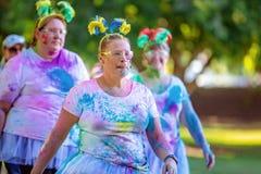 Femme marchant avec des amis dans la course d'amusement de frénésie de couleur photographie stock