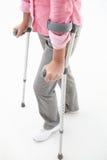 Femme marchant avec des béquilles Photographie stock