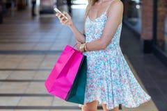 Femme marchant avec des paniers et tenant le smartphone photos stock