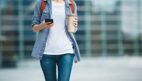 Femme marchant avec la tasse de themo de café photos libres de droits