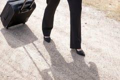 Femme marchant avec la valise de bagage de main Photos stock
