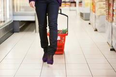 Femme marchant avec le panier à provisions images stock