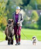 Femme marchant avec le poney et le chien photos stock