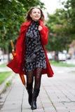 Femme marchant avec un parapluie Photo stock