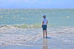 Femme marchant dans l'eau en vague déferlante Photo stock