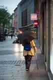 Femme marchant dans la rue avec le parapluie pendant le matin par jour pluvieux Photographie stock