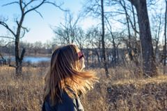 Femme marchant en bois avec les cheveux blonds soufflant en soleil image stock