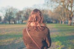 Femme marchant en parc un jour d'hiver Photographie stock libre de droits