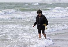 Femme marchant en ressac recherchant des coquilles de mer Image libre de droits