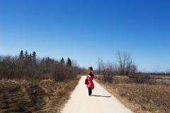 Femme marchant le long d'un itinéraire aménagé pour amateurs de la nature Photographie stock libre de droits