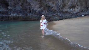 Femme marchant le long de la plage banque de vidéos