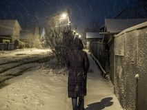 Femme marchant le long de la rue dans les chutes de neige de soirée image libre de droits