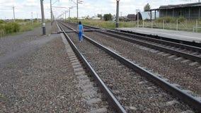 Femme marchant le long des voies ferroviaires banque de vidéos