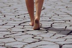 Femme marchant nu-pieds à travers la terre criquée Photos stock