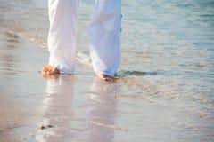 Femme marchant nu-pieds sur la plage Images libres de droits