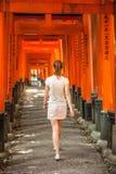Femme marchant par des portes de Torii près de Kyoto, Japon Images libres de droits