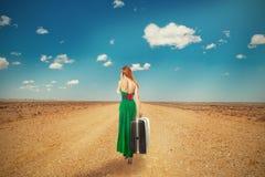 Femme marchant par le désert parlant sur la valise de transport de téléphone Photo stock