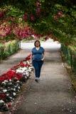 Femme marchant par un tunnel de rose images libres de droits