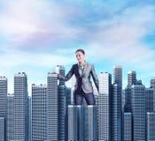 Femme marchant parmi des gratte-ciel Photos libres de droits