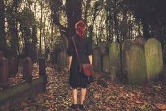 Femme marchant parmi des pierres tombales Photos stock