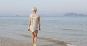 Femme marchant pour arroser sur la plage, vue arrière de dos de jeune fille banque de vidéos