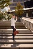Femme marchant sur des escaliers ondulant la main images stock