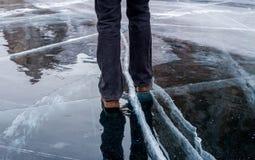 Femme marchant sur la glace criquée bleue du lac Baïkal congelé images stock