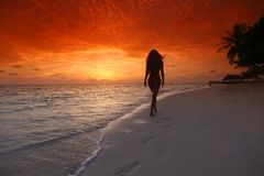 Femme marchant sur la plage Photographie stock