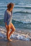 Femme marchant sur la plage au temps de coucher du soleil de la relaxation image libre de droits