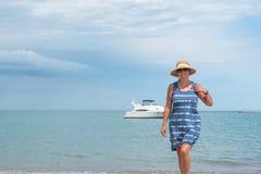 Femme marchant sur la plage avec le yacht à l'arrière-plan photos libres de droits