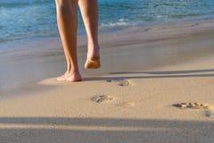Femme marchant sur la plage de sable laissant des empreintes de pas dans le sable Image stock