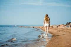 Femme marchant sur la plage de sable laissant des empreintes de pas dans le sable Photographie stock libre de droits