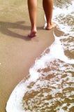 Femme marchant sur la plage de sable laissant des empreintes de pas en sable Photo stock