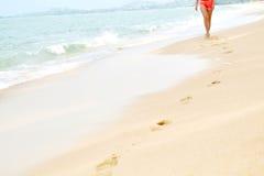 Femme marchant sur la plage, empreintes de pas en sable Style de vie sain f Images libres de droits