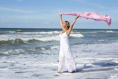 Femme marchant sur la plage et tenant un châle dans le vent Images libres de droits
