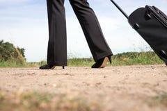 Femme marchant sur la route avec la valise de bagage de main Images libres de droits