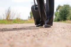 Femme marchant sur la route avec la valise de bagage de main Photos libres de droits