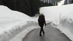 Femme marchant sur la route dans les montagnes banque de vidéos
