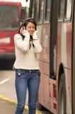 Femme marchant sur la rue de ville couvrant ses oreilles photos stock