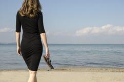 Femme marchant sur le rivage de la plage vers la mer image stock