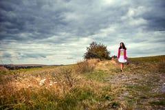 Femme marchant sur un chemin de champ Photographie stock libre de droits