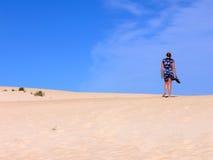Femme marchant sur une plage Photographie stock